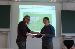 Matijs Moree (student WUR) draagt het rapport in de vorm van een USB-stick over aan Thijs Fijen (Regelink Ecologie & Landschap).